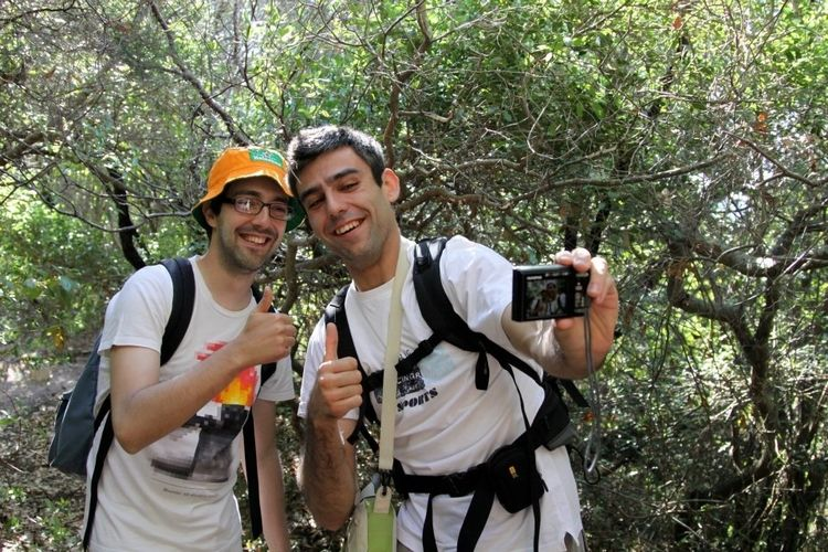Ricardo Ferreira and José Caldeira, by a tree, taking a selfie with a camera